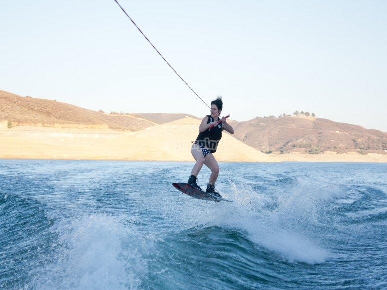 Saltando sobre ola con tabla de wake