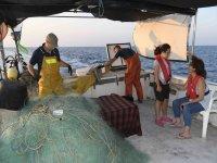 Turisti che imparano il lavoro del pescatore