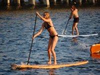 dos chicas practicando sup en el mar
