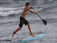 nino practicando paddle surf en el mar