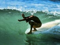 hombre agachado mientras surfea