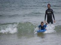 un monitor che insegna a un bambino a surf.jpeg
