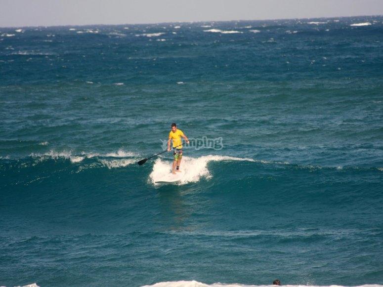 Cogiendo ola con tabla de SUP