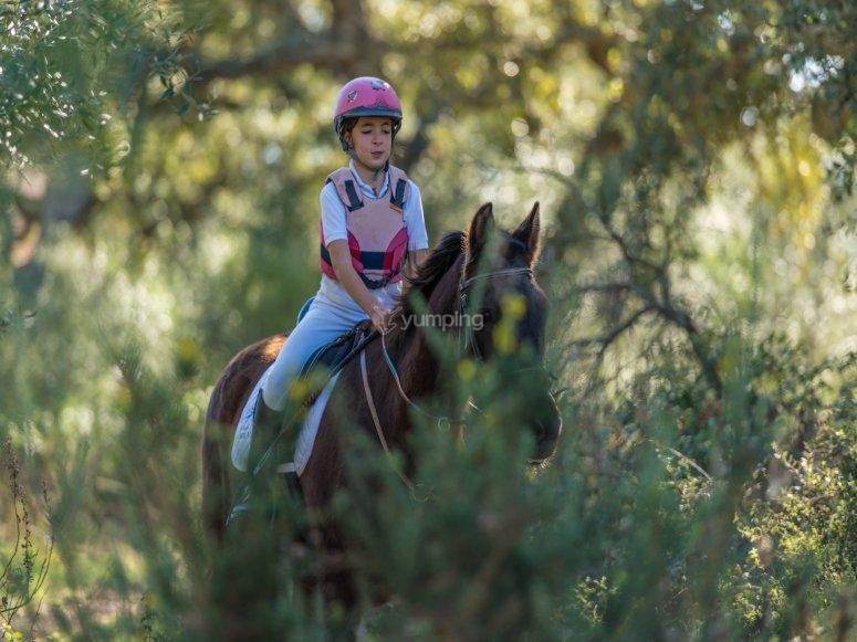 Girl riding a horse through the mountains