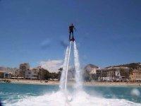 hombre practicando flyboard con un pueblo de fondo