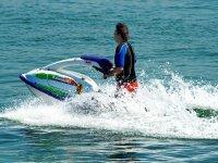 hombre empujando una moto de agua en el mar