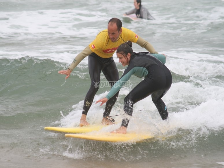 Instructor and girl learning how to surf in Somo