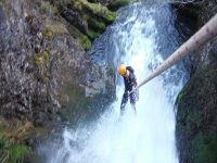 man descending a ravine with whitewater