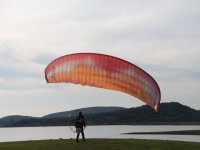 滑翔伞的人要在一个滑翔机飞行起飞,日落