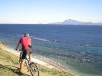 hombre en bicicleta mirando el mar