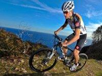 男子骑着山地自行车与海在背景中