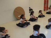 ninas en una clase de baile sentadas en el suelo