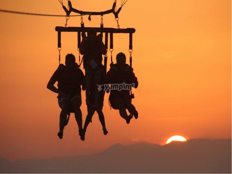 Volando en parasailing puesta de sol