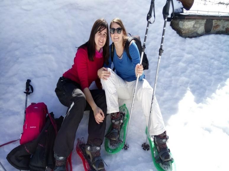 Amigas descansando en la nieve con las raquetas