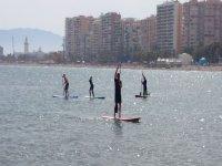 cinco personas navegando en sup