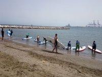 entrando en el agua para practicar paddle surf
