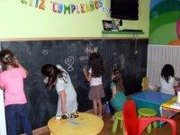 ninas pintando en una gran pizarra