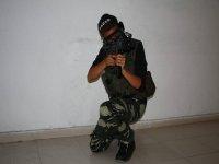 chico agachado con una replica de airsoft