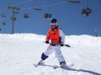 NIña aprendiendo a esquiar en pista verde