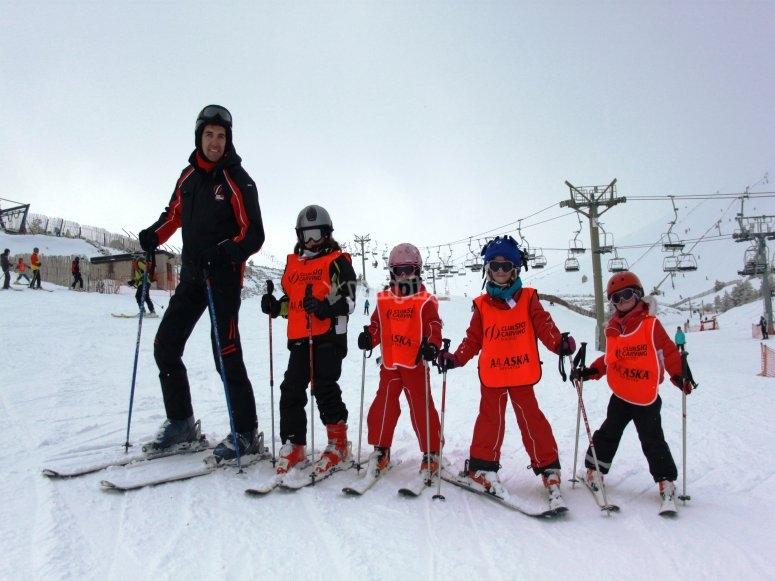 Monitor y alumnos pequeños de esquí