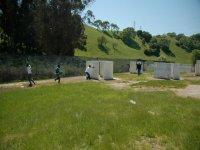 jugando al paintball en un campo lleno de obstaculos