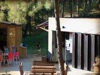 mesas de madera para comer con un edificio blanco de fondo