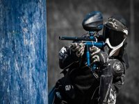 man behind a wall playing paintball