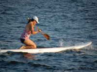 woman paddling on a surfboard