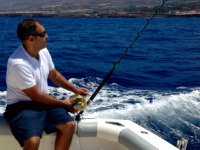 Pescando sentado en el borde del barco