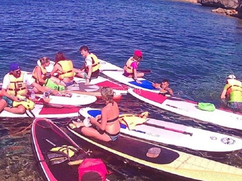 El grupo sentado sobre la tabla de paddle surf