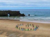 Estiramientos en la orilla antes de la clase de surf