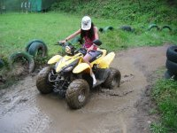 Chica pilotando el quad sobre barro