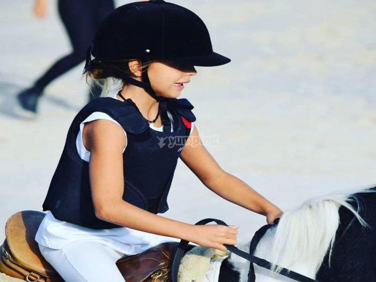 Pequeña jinete sobre el caballo