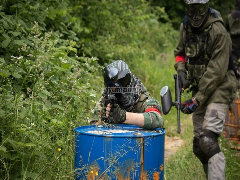 Colleagues covering themselves in paintball game