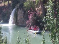 children practicing rafting in a landscape with waterfall