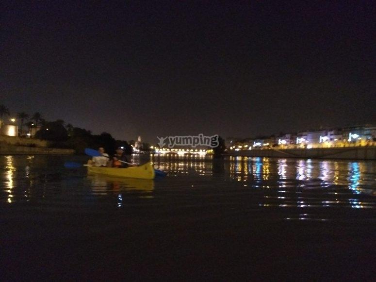 Canoa attraverso Siviglia di notte