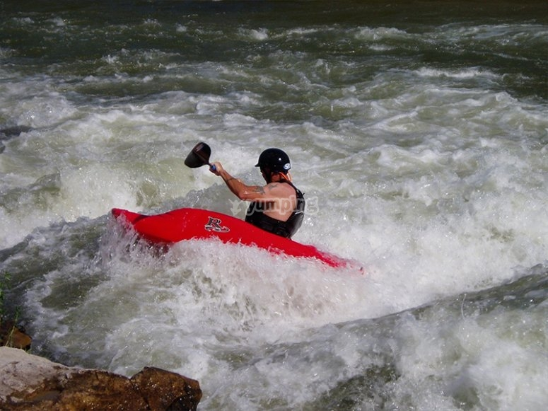 Practicando piraguismo en aguas bravas
