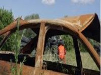 rusty car and behind him a boy playing paintball.jpg