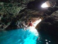 Niño en kayak atravesando una cueva