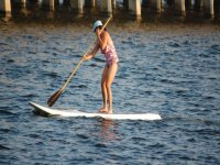 mujer practicando paddle surf en una tabla blanca