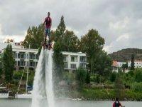 chico practicando flyboard mientras uno le mira desde una moto de agua