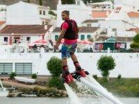 hombre en flyboard con casas blancas de fondo