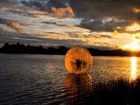 在海面上的巨型球徽标与夕阳女孩