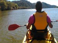 man on his back sailing in kayak