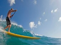 boy practicing paddle surfing with strong waves