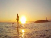 man practicing paddle surfing on a sunset