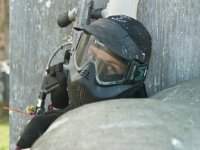 girl behind a sack playing paintball