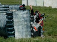 boys with hands raised while playing paintball
