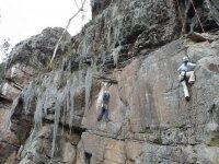 dos chicos escalando una roca natural
