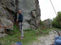 en el suelo junto a una roca para escalar